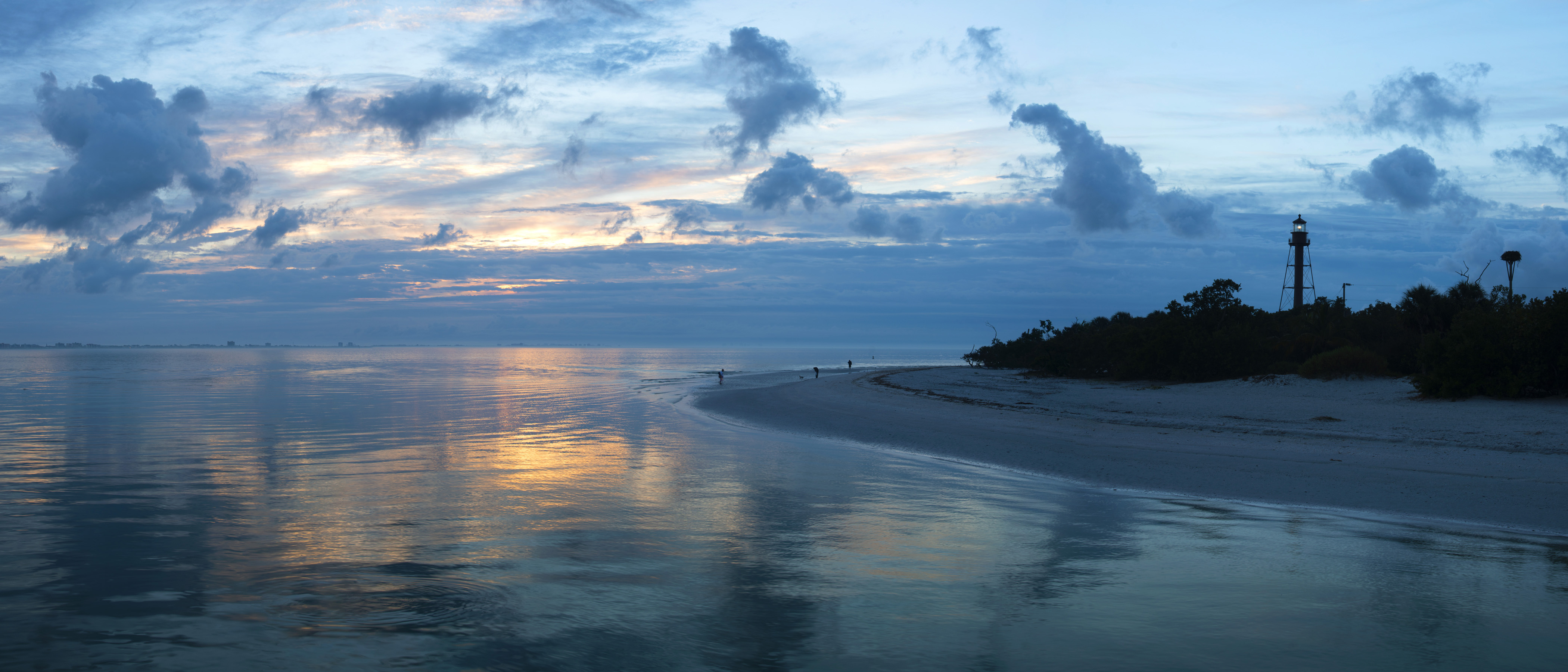 yellow and blue light during sunset over the ocean and Sanibel Island in Florida. The water is calm and serene.