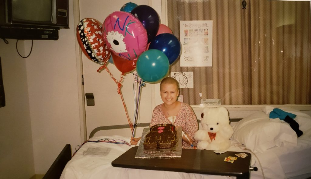 A childhood leukemia survivor celebrates finishing treatment with a cake and balloons.