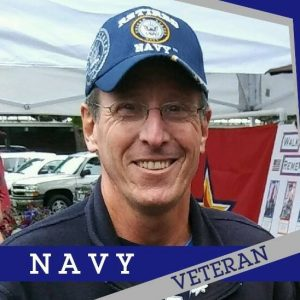 "A retired Navy Veteran and colon cancer survivor Daniel ""Dry Dock"" Shockley smiles while wearing a blue Navy hat"