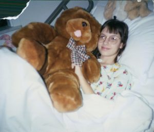 Carolyn, a childhood cancer survivor, holds a teddy bear in a hospital bed.