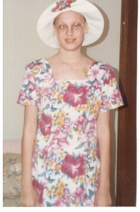 Carolyn, a childhood cancer survivor, smiles in a summer dress.